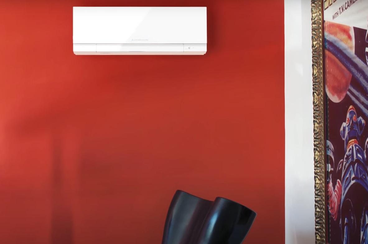 Na obrazku znajduje się Klimatyzacja split Mitsubishi z serii M w kolorze białym, znajdująca się na czerwonej ścianie.