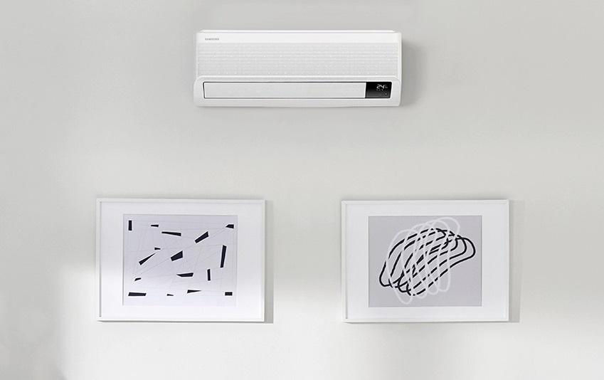 Na obrazku znajduje się Klimatyzator Samsung w kolorze białym umieszczony na białej ścianie w towarzystwie dwóch obrazów.