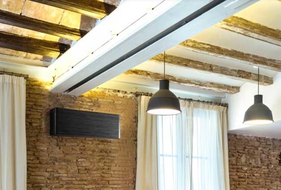 Na zdjęciu znajduje się Klimatyzator Daikin zamontowany na ceglanej ścianie pomieszczenia.
