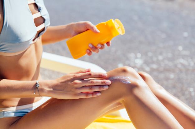 Na obrazku znajduje się kobieta korzystająca z kremu z filtrami UV.